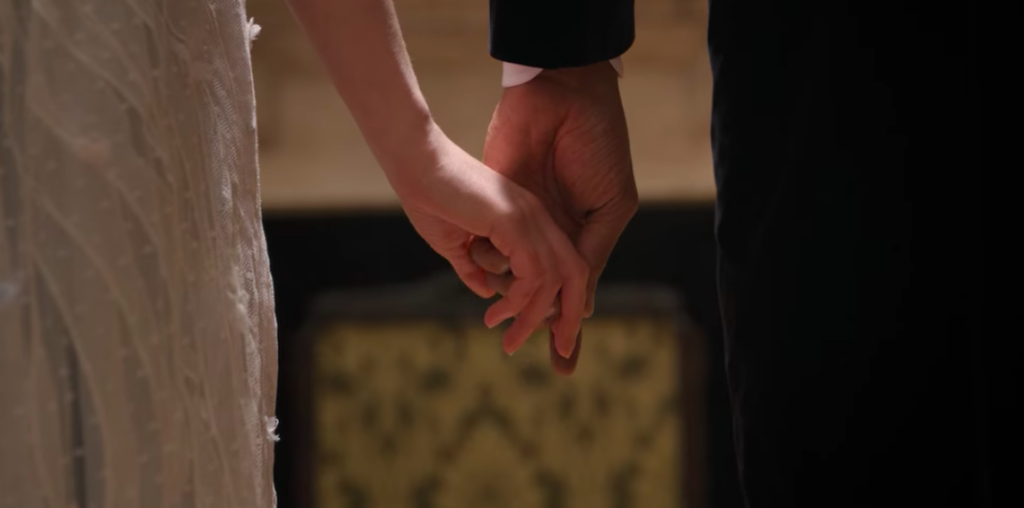 Simon and Daphne's hands touching.